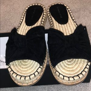 Suede bow espadrille slides with studded detail.